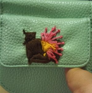 A green leather wallet with embroidery of a camera and a flower going through the lense.